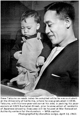Dave Tatsuno re-reads notes he compiled while he was a student at the University of California, where he was graduated in 1936. Tatsuno, with his two-year-old son at his side, is packing his possessions at 1625 Buchanan Street, prior to evacuation of residents of Japanese ancestry. Evacuees will be housed at War Relocation Authority centers for duration.  -- WRA caption. Photographed by Dorothea Lange,  San Francisco, April 13, 1942.